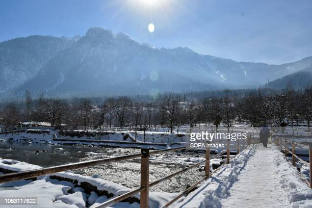 Kashmiri girl seen walking through a snow covered foot bridge during a sunny winter day in Ganderbal about 50kms from Srinagar Indian administered...
