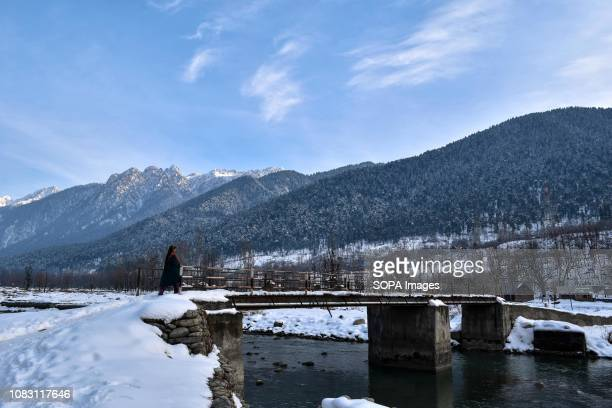 Kashmiri girl seen walking through snow next to a bridge during a sunny winter day in Ganderbal about 50kms from Srinagar Indian administered Kashmir...
