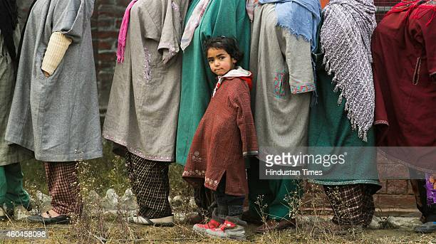 Kashmiri girl stands among adults waiting in a queue to cast their votes during the fourth phase polling of the Jammu and Kashmir state elections in...