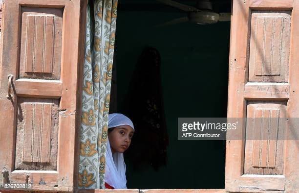 A Kashmiri girl watches the funeral procession of slain rebel Abid Ahmed in the village of Hajinar in the district Bandipora north of Srinagar on...