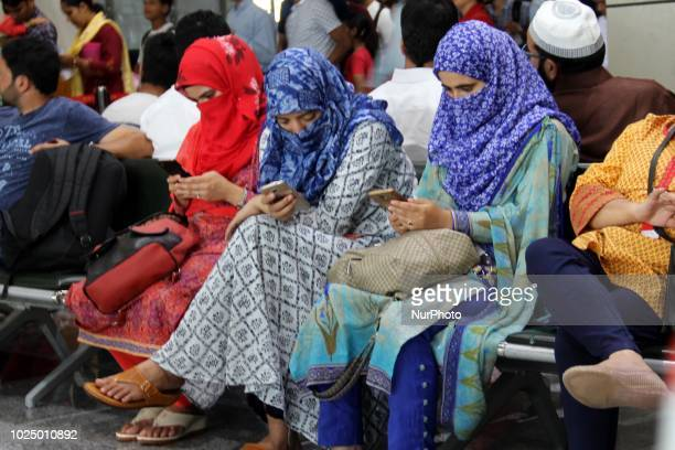 Kashmiri Girls Using Mobile Phones as they wait for their Flight at Srinagar Airport