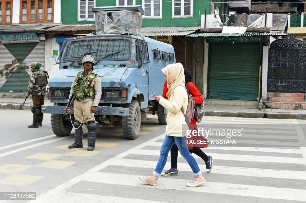 Kashmiri girls walk past Indian paramilitary troopers standing guard in Srinagar on March 1 2019 While Pakistan's promised release of an Indian pilot...