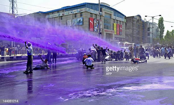 Kashmiri government employees are sprayed with purple colored water by Indian police to disperse a protest in Srinagar on May 9,, 2012. Indian police...