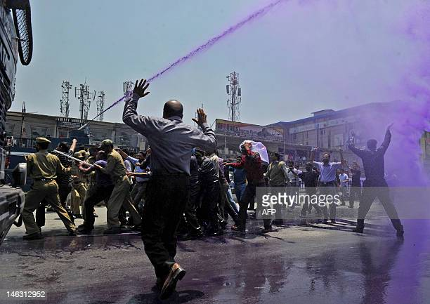 Kashmiri government employees demonstrate while riot police unleash purple-dyed water cannon to disperse a protest in Srinagar on June 14, 2012....