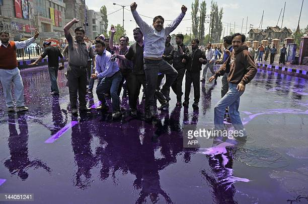 Kashmiri government employees shout anti government slogans after Indian police sprayed purple colored water to disperse a protest in Srinagar on May...