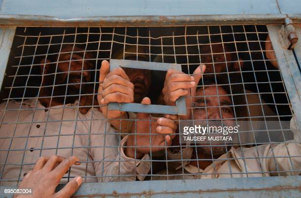 Kashmiri government employees shout antigovernment slogans inside a police vehicle as they are detained by security personnel during a protest in...