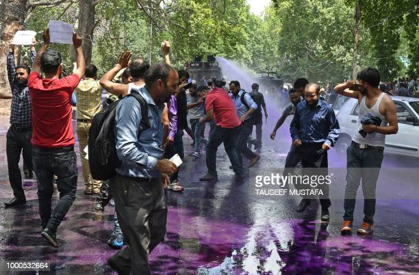 Kashmiri government teachers shout anti government slogans as Indian police spray purple coloured water in Srinagar on July 17 2018 Dozens of...