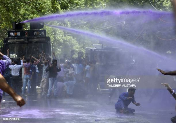 TOPSHOT Kashmiri government teachers shout anti government slogans as Indian police spray purple coloured water during a protest in Srinagar on July...