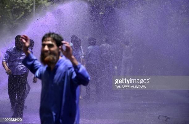 Kashmiri government teachers shout anti government slogans as Indian police spray purple coloured water during a protest in Srinagar on July 17 2018...