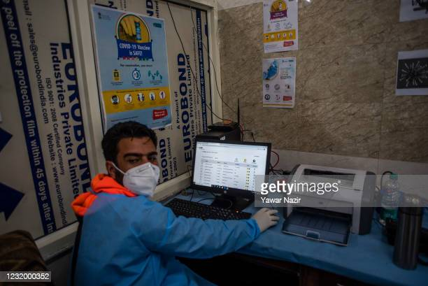 Kashmiri healthcare worker enters the names of the people after vaccination at a hospital on March 29, 2021 in Srinagar, the summer capital of Indian...