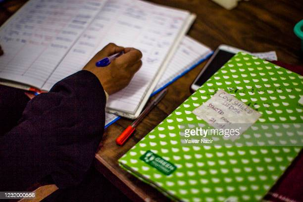 Kashmiri healthcare worker registers the names of the people after vaccination at a hospital on March 29, 2021 in Srinagar, the summer capital of...
