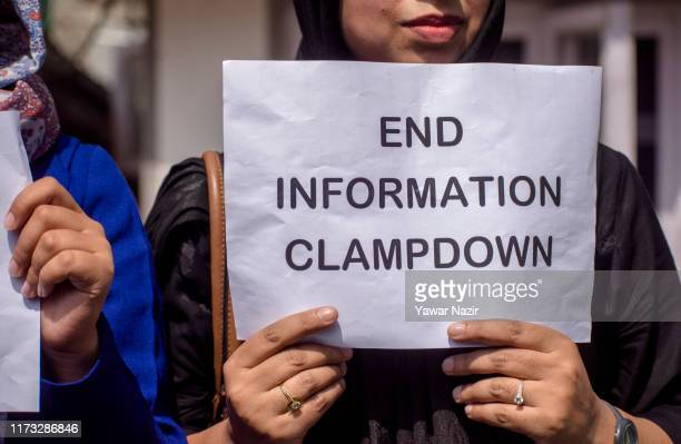 Kashmiri journalist holds a placard as she protests against the continued communication blockade by the Indian authorities after the revocation of...
