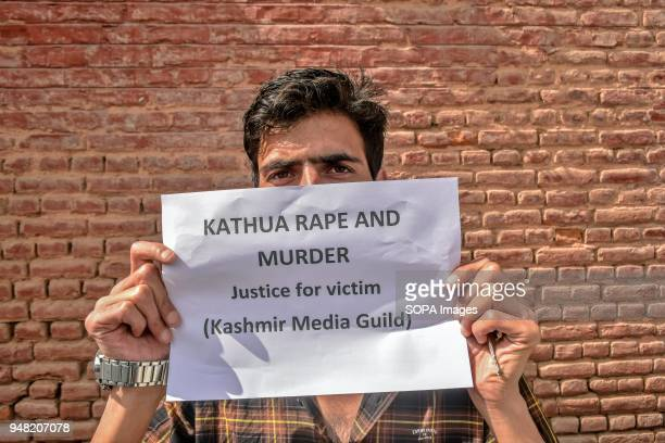 Kashmiri journalist holds a placard during a protest against the rape and murder of an eightyearold girl in Srinagar Indian administered Kashmir...