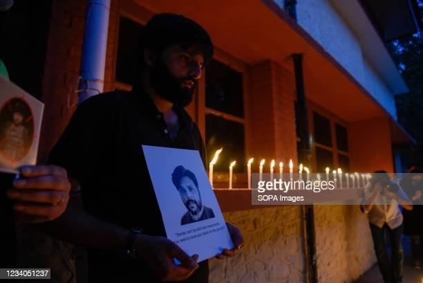 Kashmiri journalist holds a portrait of Danish Siddiqui during a candle light vigil in Srinagar. Reuters journalist Danish Siddiqui was killed on...