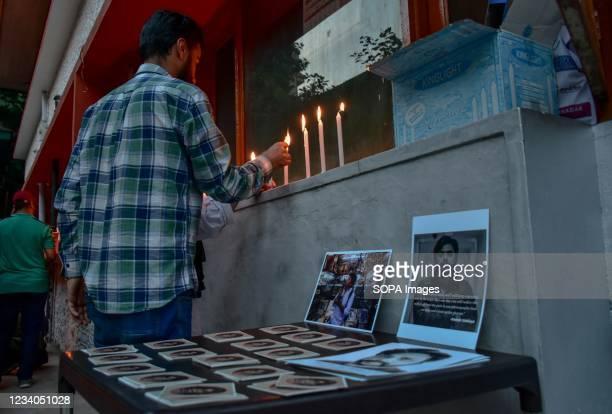 Kashmiri journalist lights candles as he pays homage to slain Reuters journalist Danish Siddiqui, during a candle light vigil at Kashmir Press Club...