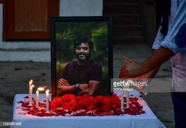 Kashmiri journalist lights candles near the portrait of slain Reuters journalist Danish Siddiqui, during a candle light vigil at Kashmir Press Club...