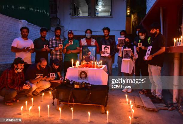 Kashmiri journalists hold placards and portraits of slain Reuters journalist Danish Siddiqui, during a candle light vigil at Kashmir Press Club in...