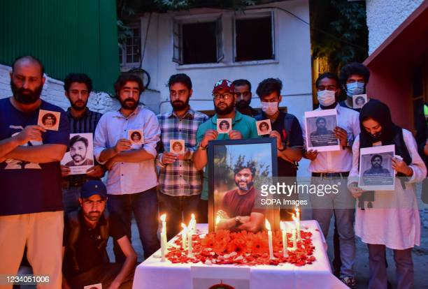 Kashmiri journalists hold placards as they pay homage to slain Reuters journalist Danish Siddiqui, during a candle light vigil at Kashmir Press Club...