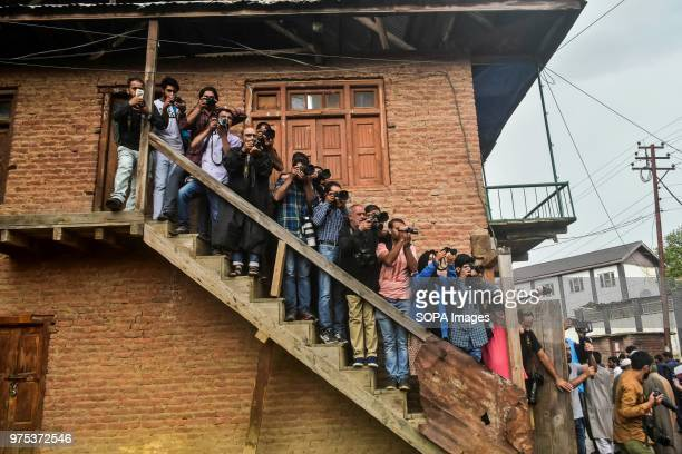 Kashmiri journalists take pictures during a funeral procession for Shujaat Bukhari veteran journalist and EditorinChief of English daily 'Rising...