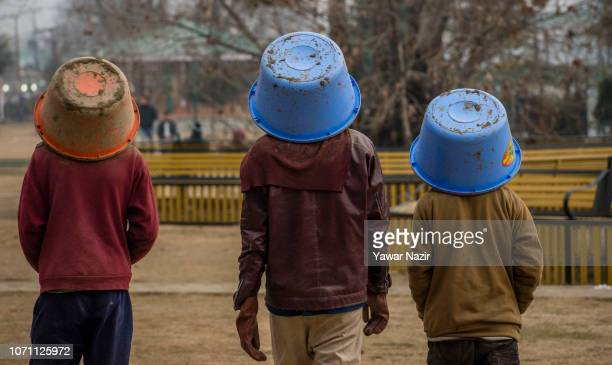 Kashmiri labourers cover their heads with buckets after dumping soil at the river bank during a cold day on December 10 2018 in Srinagar the summer...