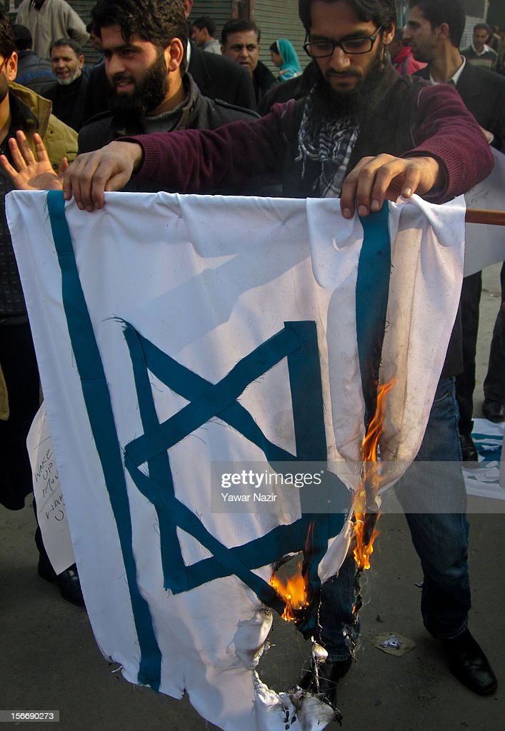 Kashmiri Lawyers set an Israeli flag on fire while holding placards during a protest against Israel and in solidarity with Palestine in the city centre on November 19, 2012 in Srinagar, the summer capital of Indian administered Kashmir, India. Dozens of Lawyers took to the streets and set a blaze Israeli flags to protest against the recent air strikes in the Gaza region.