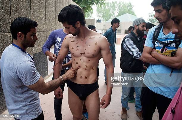Kashmiri man applies gloss to a body builder before participating in 'Mr Kashmir Body Building Competition' organized by Jammu and Kashmir...