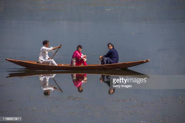 Kashmiri man ferries women in his rowing boat at the Dal lake during curfew like restrictions on September 09 2019 in Srinagar the summer capital of...