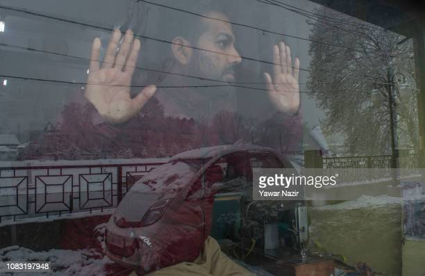 Kashmiri man look towards the snow flakes during a fresh snow fall on January 16 2019 in Srinagar the summer capital of Indian administered Kashmir...