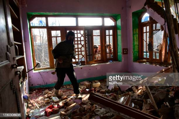 Kashmiri man looks for belongings iniside a damaged residential house in Kanigam Village of Shopian district, South of Srinagar, Indian Administered...