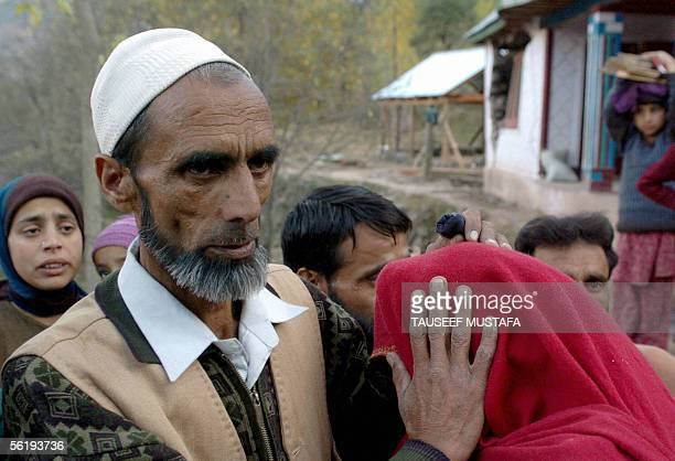 Kashmiri man Mohammed Farid Khan is embraced by a relative in Uri some 120 kms north of Srinagar17 November 2004 after returning from Pakistan...
