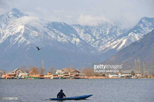 A Kashmiri man paddles his boat in Dal Lake in Srinagar on February 26 2019 Indian warplanes breached Pakistani airspace on February 26 in a move...
