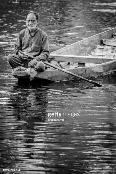 a kashmiri man paddling a shikara (traditional boat) on dal lake of kashmir. - shaifulzamri stock pictures, royalty-free photos & images