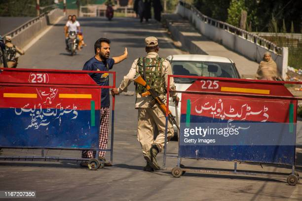 Kashmiri man pleads an Indian paramilitary trooper to allow him to cross the barrier during curfew like restrictions on September 10 2019 in Srinagar...