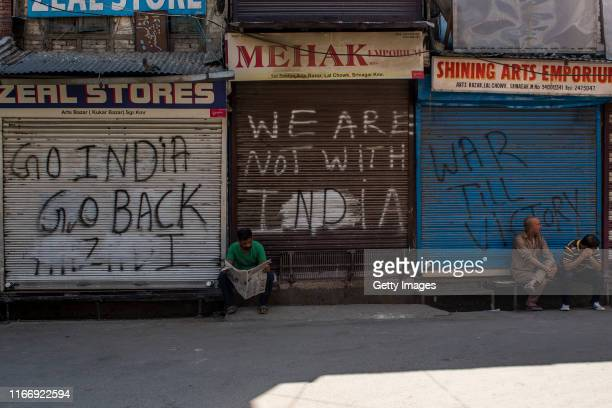 Kashmiri man reads a newspaper in front of closed shops covered with graffiti in the closed commercial hub of the city center during curfew like...
