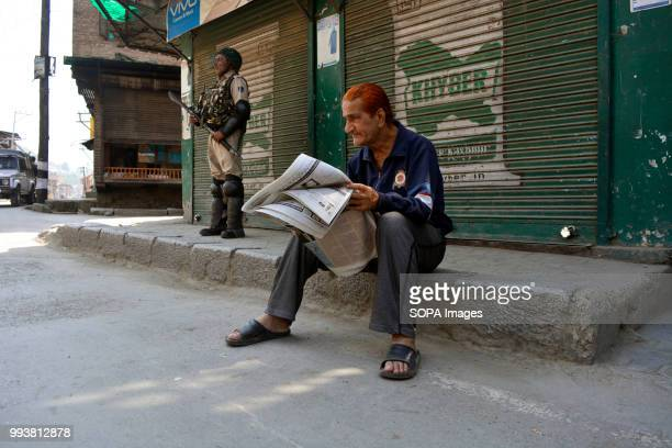 Kashmiri man reads newspaper on the porch of shuttered shop as an Indian government trooper stands guard during a curfew restrictions on the second...