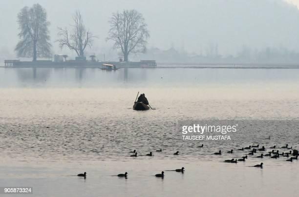 Kashmiri man rows a boat across Dal Lake in Srinagar on January 17 2018 / AFP PHOTO / TAUSEEF MUSTAFA