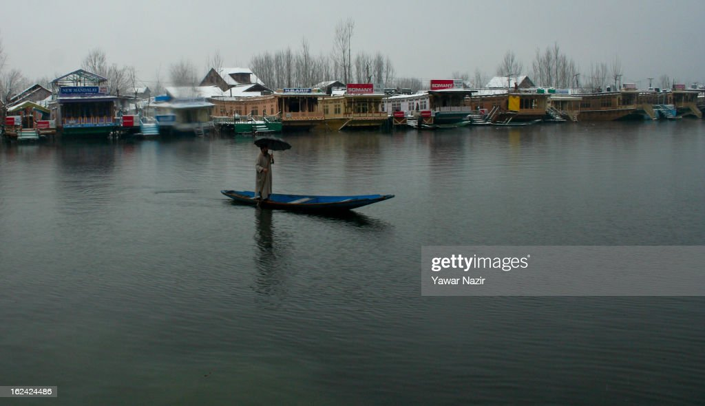 A Kashmiri man rows his boat on the waters of Dal lake after a snowfall on February 23, 2013 in Srinagar, Indian Administered Kashmir, India. Several parts of the Kashmir Valley, including the summer capital Srinagar, experienced fresh snowfall today, prompting the authorities to issue an avalanche warning and leading to closure of the Jammu-Srinagar Highway, the only road link between Kashmir and rest of India.