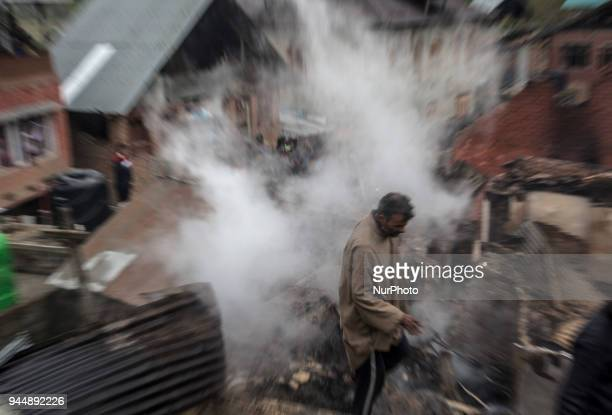 A Kashmiri man searches the debris of a house after a gunfight between rebels and government forces Wednesday April 11 in Khudwani village about 60...