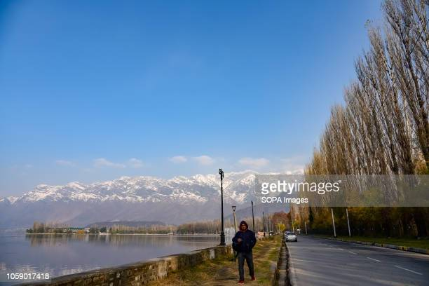 Kashmiri man seen walking on the shore of Dal Lake in Srinagar during the autumn season Kashmir has been divided between India and Pakistan since...