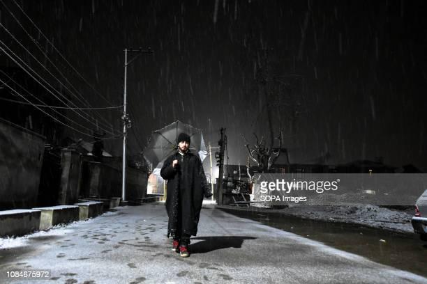 Kashmiri man seen walking through a street during fresh snowfall in Srinagar Indian administered Kashmir Fresh snowfall started across the Kashmir...