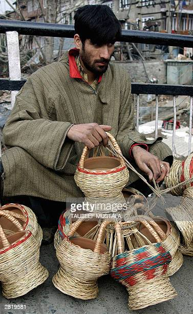 Kashmiri man sells small earthenware bowls held in a wickerwork frame called Kanger which once filled with burning charcoal are used as heater in...
