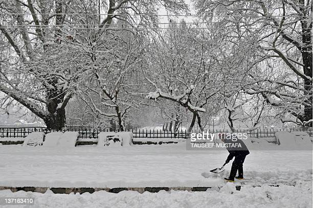 Kashmiri man shovels a sidewalk during snowfall in Srinagar on January 16, 2012. A cold wave further tightened its grip in Jammu and Kashmir with...