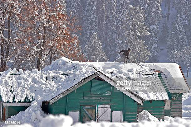 A Kashmiri man shovels snow from a cabin roof in Gulmarg situated about 55 kms north of Srinagar on January 13 2012 Gulmarg is the main ski...