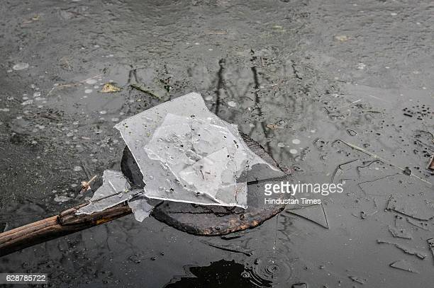 Kashmiri man shows a piece of frozen ice in the interiors of Dal Lake on December 9 2016 in Srinagar India The weather in the region continued to...