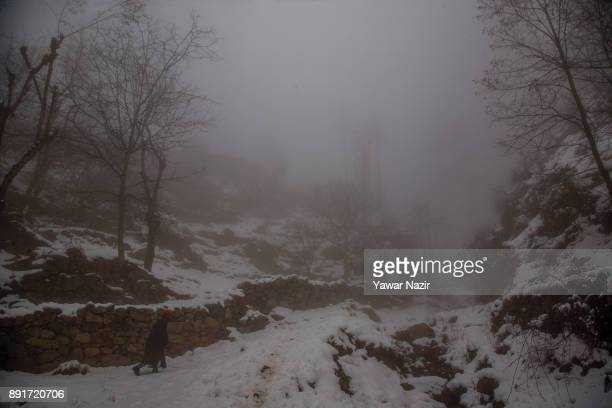 Kashmiri man walk toward his home on a snow covered mountain trail amid dense fog after seasons first snowfall on December 13 2017In the outskirts of...