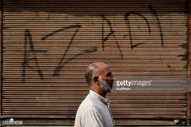 A Kashmiri man walks past a closed shop during protests after friday prayers in Srinagar Indian Administered Kashmir on 27 September 2019 People were...
