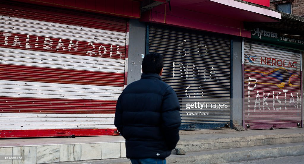 A Kashmiri man walks past graffiti written on shops by Kashmiri protesters during a strike call given by separatists against the execution of alleged Indian parliament attacker Mohammad Afzal Guru on February 17, 2013 in Srinagar, the summer capital of Indian Administered Kashmir, India. Normal life remains affected in Indian-administered Kashmir for the ninth consecutive day as a complete shutdown was observed on the call of separatist leader Syed Ali Shah Geelani. Afzal Guru was hanged on February 9 for his alleged role in the 2001 Indian parliament attack which left 14 dead. Clashes between Kashmiri youth and Indian police were also reported in several parts of the disputed Himalayan region, which was put under a strict curfew for a week by Indian authorities worried about massive public protests following Guru's hanging last Saturday.