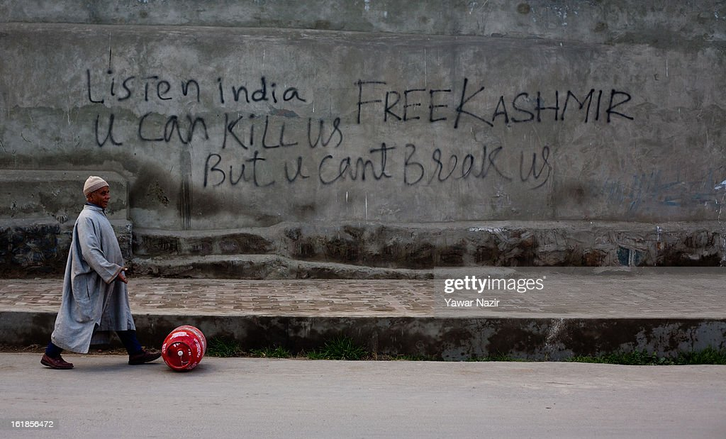 A Kashmiri man walks past graffiti written on the wall by Kashmiri protesters during a strike call given by separatists against the execution of alleged Indian parliament attacker Mohammad Afzal Guru on February 17, 2013 in Srinagar, the summer capital of Indian Administered Kashmir, India. Normal life remains affected in Indian-administered Kashmir for the ninth consecutive day as a complete shutdown was observed on the call of separatist leader Syed Ali Shah Geelani. Afzal Guru was hanged on February 9 for his alleged role in the 2001 Indian parliament attack which left 14 dead. Clashes between Kashmiri youth and Indian police were also reported in several parts of the disputed Himalayan region, which was put under a strict curfew for a week by Indian authorities worried about massive public protests following Guru's hanging last Saturday.