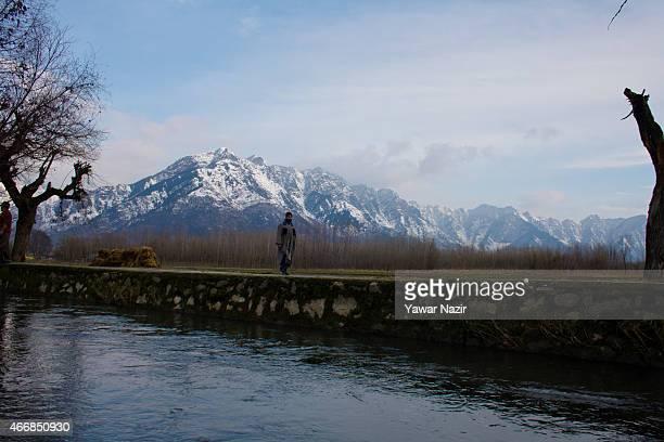 Kashmiri man walks past snow capped Zabarvan mountains on March 19 2015 in Srinagar the summer capital of Indian administered Kashmir India Kashmir...
