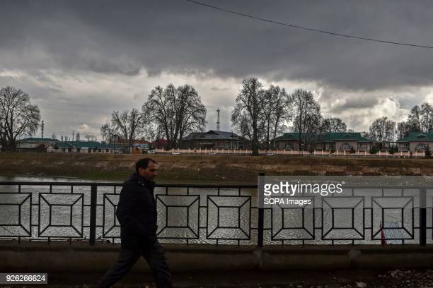Kashmiri man walks through a street on a partly cloudy day in Srinagar Indian administered Kashmir Ahead of prediction of rain and snow from Thursday...
